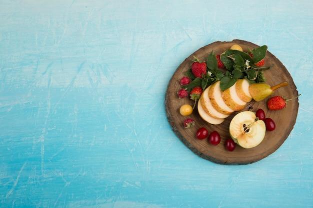 Piatto di frutta rotondo con pere, mele e frutti di bosco nel lato destro