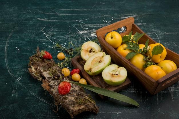 Piatto di frutta rotondo con pere, mele e frutti di bosco su sfondo opaco
