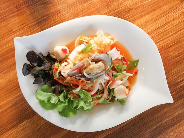 Piatto di frutti di mare piccante mescolare insalata con gamberi cozza di calamari e verdure fresche servite sul tavolo da pranzo