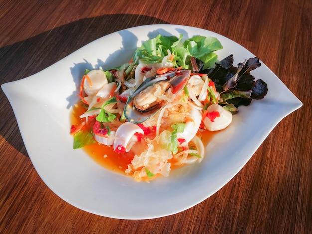 Piatto di frutti di mare piccante mix di insalata con gamberetti cozze squid e verdure fresche