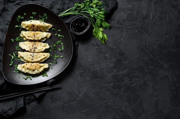 Piatto di gnocchi coreani fritti sulla tavola nera rustica. vista dall'alto. spazio per il testo