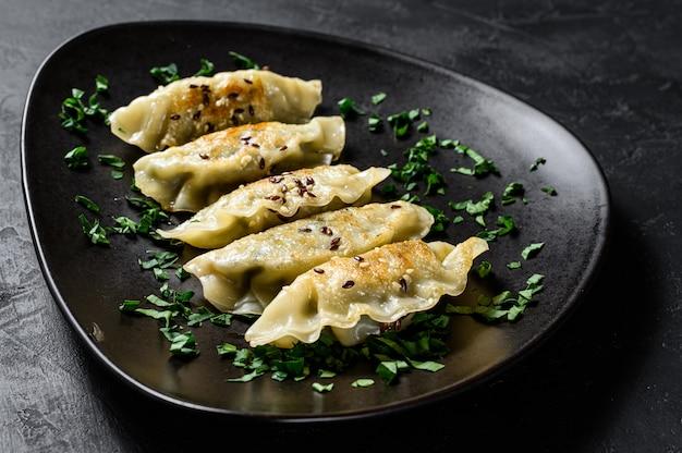 Piatto di gnocchi coreani fritti sulla tavola nera rustica