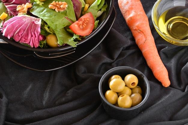 Piatto di insalata con lattuga, pomodoro, olive e olio. su un panno nero