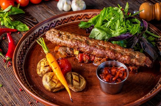 Piatto di kebab tradizionale turco e arabo, kebab di agnello e manzo con verdure al forno, funghi e salsa di pomodoro