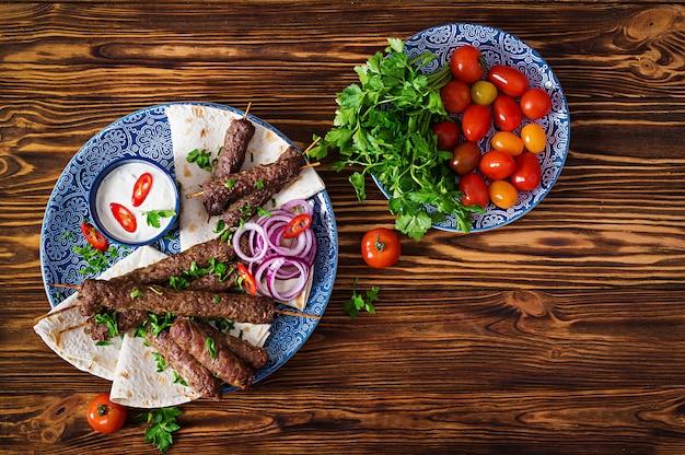 Piatto di kebab tradizionale turco e arabo ramadan mix. kebab adana, pollo, agnello e manzo su pane lavash con salsa.