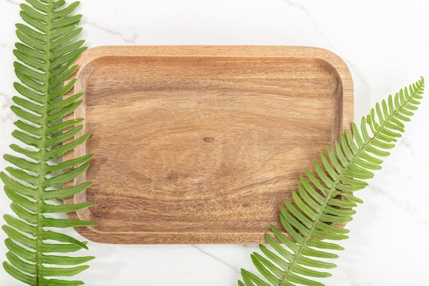 Piatto di laici vassoio in legno e foglie verdi su marmo bianco sullo sfondo. modello