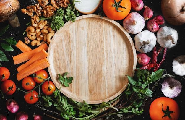 Piatto di legno che circonda con alimento sano fresco su legno nero