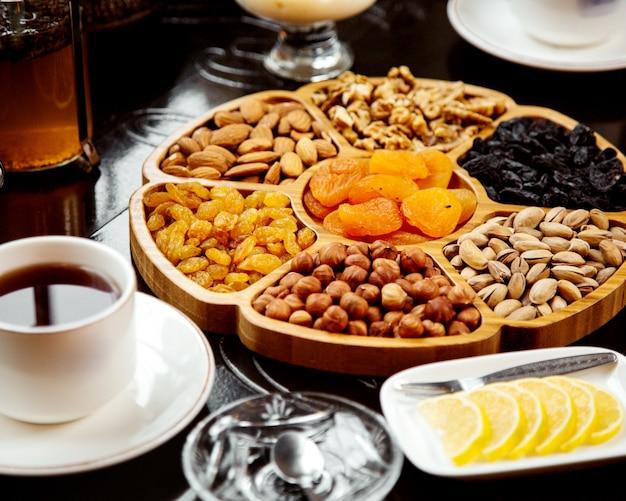 Piatto di legno con frutta secca e noci
