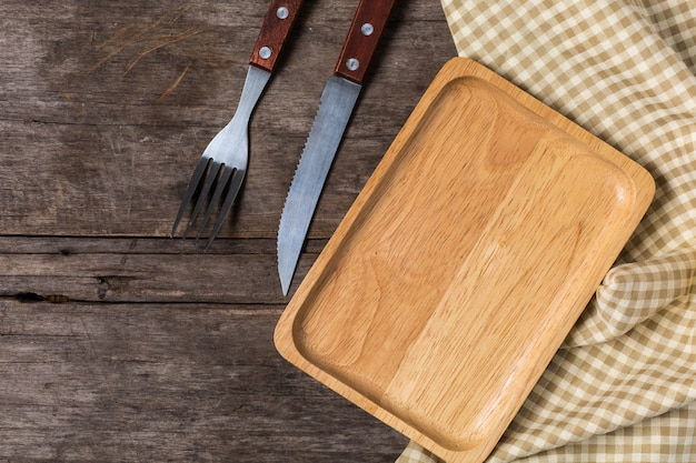Piatto di legno con il coltello da bistecca su fondo di legno