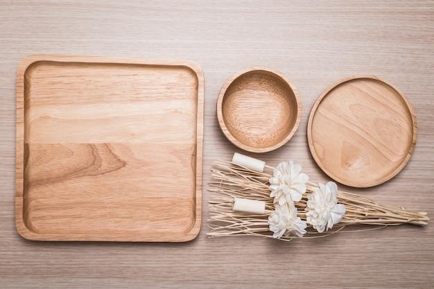 Piatto di legno con il fiore secco sui precedenti di legno.