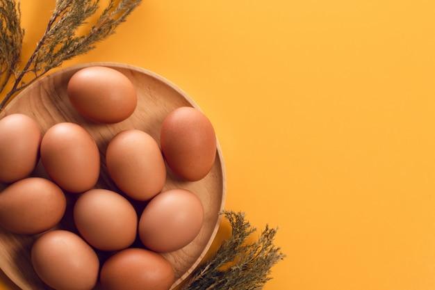 Piatto di legno con l'alimento dell'uovo di pasqua e fiore secco sulla vista superiore del fondo giallo di stile d'annata