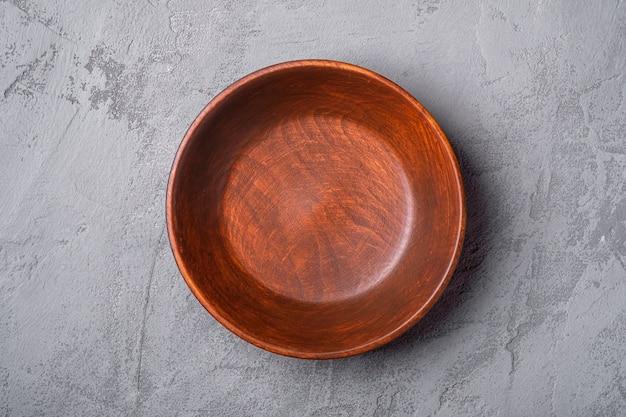 Piatto di legno marrone artigianale rotondo vuoto su pietra