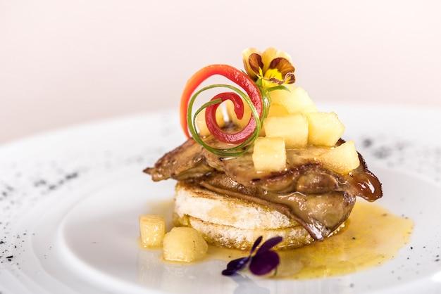 Piatto di lusso con fegato d'anatra, pezzi di ananas e mango, salsa dolce, tostato