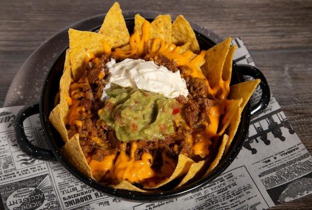 Piatto di nachos con peperoncino, panna acida guacamole e salsa cheddar sul tavolo di legno. immagine isolata