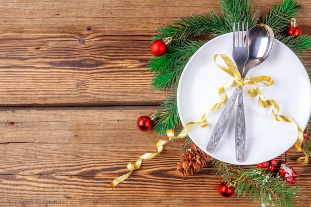 Piatto di natale bianco con la forchetta e cucchiaio, rami del pino con le decorazioni di natale su fondo di legno