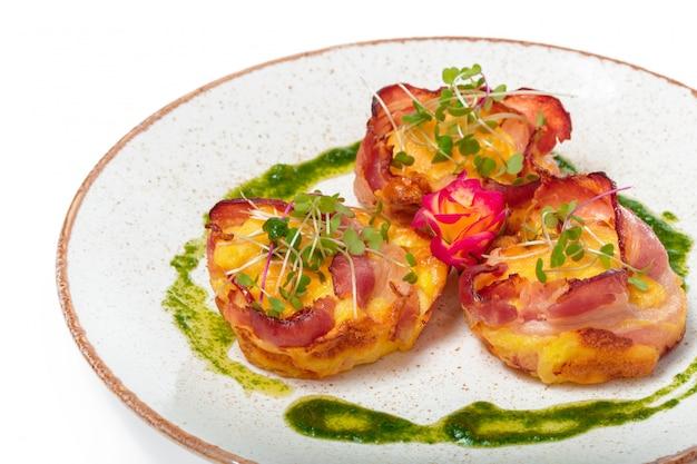 Piatto di pancetta avvolto capesante in file ordinate su un piatto di colore chiaro