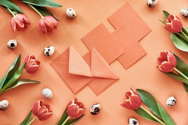 Piatto di pasqua disteso su carta arancione con tulipani, uova di quaglia, biglietti di auguri e buste