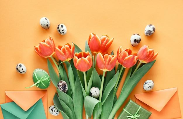 Piatto di pasqua disteso su carta arancione. uova dipinte, carte regalo, buste e scatole regalo