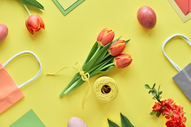 Piatto di pasqua giaceva su carta gialla. mazzo di tulipani, scatole regalo, uova decorative e sacchetti di carta, disposizione geometrica