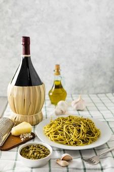Piatto di pasta con bottiglia di vino e olio d'oliva