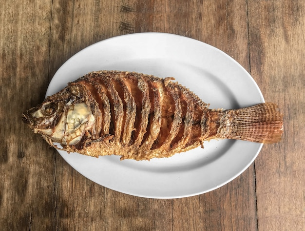 Piatto di pesce infornato di tilapia sul fondo di legno della tavola.
