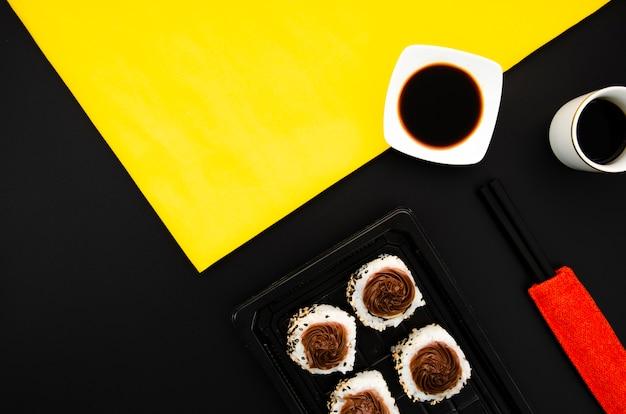 Piatto di pietra con rotoli di sushi su uno sfondo nero con ciotola di salsa di soia su sfondo giallo