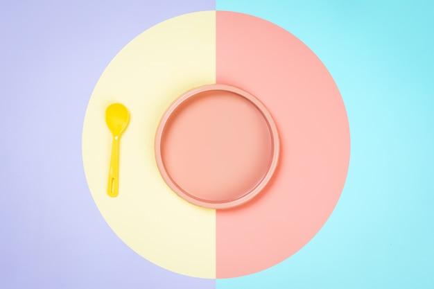 Piatto di plastica rosa, blu e un cucchiaio giallo in uno sfondo giallo-rosa isolato.