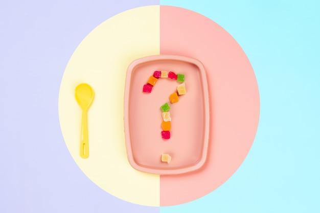 Piatto di plastica rosa su cui è un punto interrogativo di ananas candito e un cucchiaio giallo in uno sfondo giallo-rosa isolato.