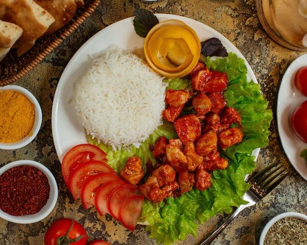Piatto di pollo con pezzi di pollo in salsa di pomodoro servito con riso e pomodori