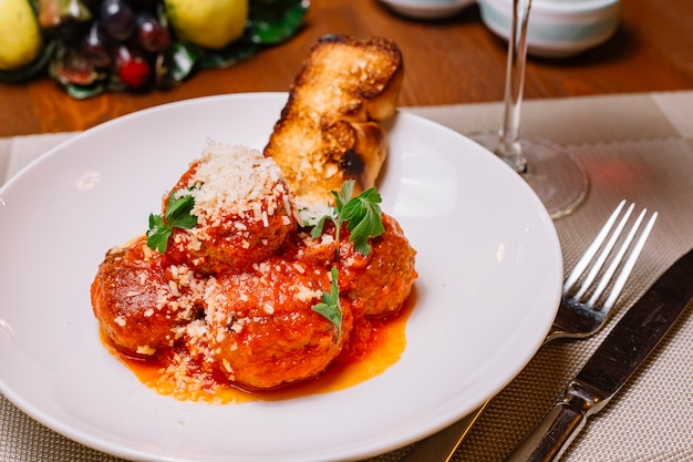Piatto di polpette guarnito con salsa di pomodoro grattugiato parmigiano e prezzemolo servito con pane tostato