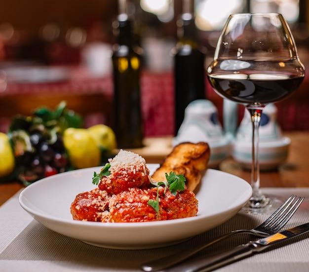 Piatto di polpette guarnito con salsa di pomodoro grattugiato parmigiano e prezzemolo servito con vino rosso