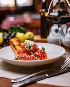Piatto di polpette guarnito con salsa di pomodoro grattugiato parmigiano e prezzemolo