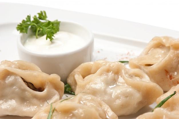 Piatto di ravioli con panna acida isolato su bianco