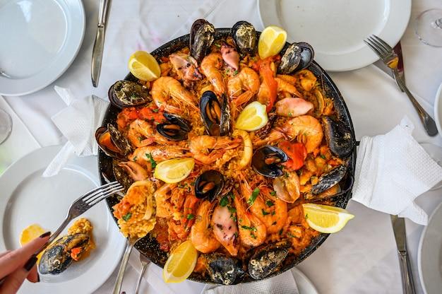 Piatto di riso alla paella di pesce spagnolo con gamberi freschi, scampi, cozze, calamari, polpi e capesante servito in padella. il cameriere mette una porzione sul piatto. vista dall'alto. ristorante