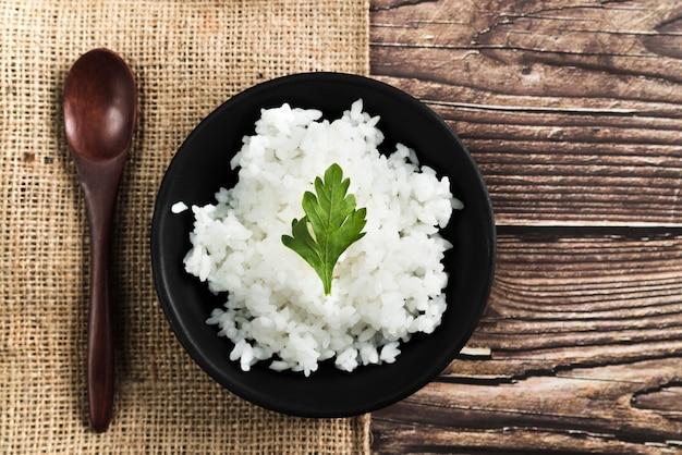 Piatto di riso con prezzemolo vicino a cucchiaio di legno e tela di sacco