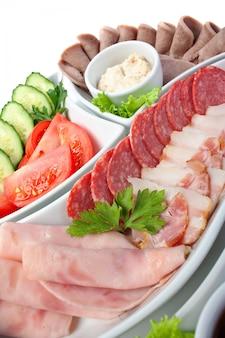 Piatto di salsicce assortite e verdure isolate su bianco
