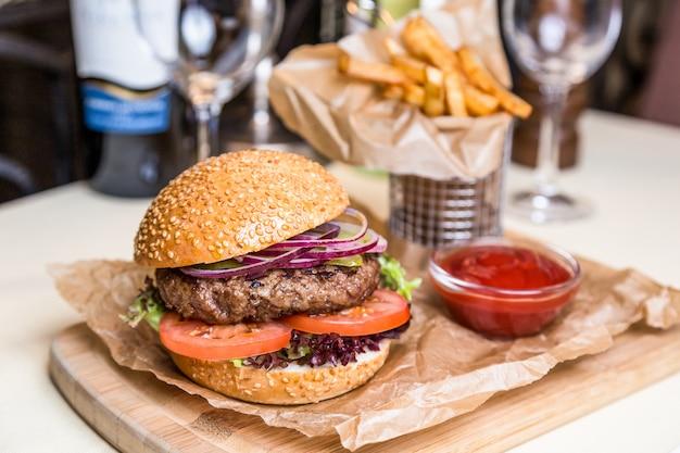 Piatto di servizio del ristorante - hamburger con la cotoletta con la patata fritta sul bordo di legno