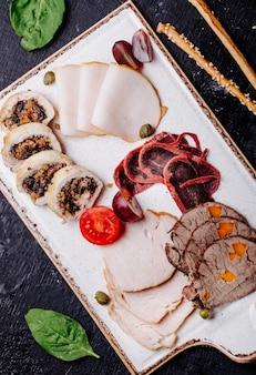 Piatto di snack per aperitivi con involtini di carne di tacchino prosciutto affumicato faro e pomodoro.