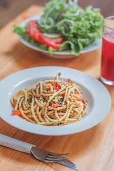 Piatto di spaghetti con verdure wok e insalata fresca in un ristorante. avvicinamento.