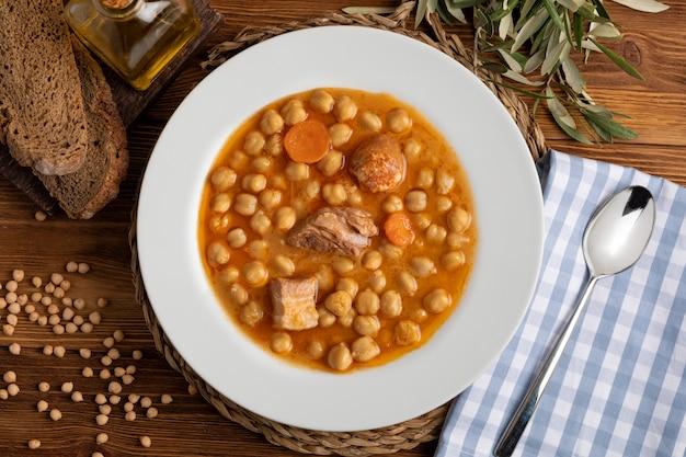 Piatto di stufato di ceci con manzo, salsiccia, pancetta, carote e olio d'oliva