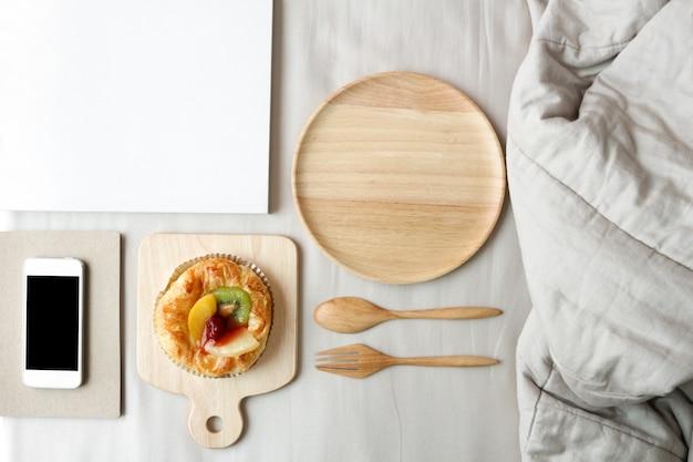 Piatto di torte di frutta mista è in cima al letto. colazione a letto concetto.