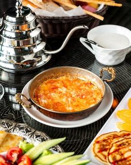 Piatto di uova con pomodoro servito in padella di rame turco