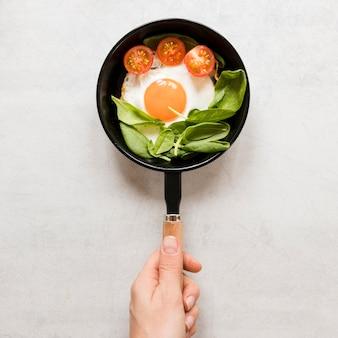 Piatto di uova fritte in padella con pomodori