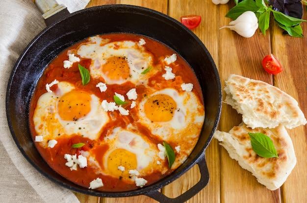Piatto di uova in camicia con salsa di pomodori, peperoncino e cipolle