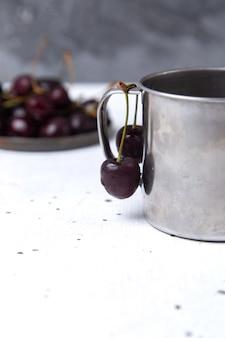 Piatto di vista frontale con ciliegie scure fresche acide e pastose su grigio