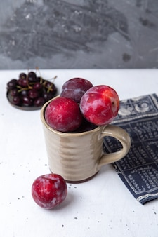 Piatto di vista frontale con ciliegie scure fresche aspre e pastose con prugne su grigio