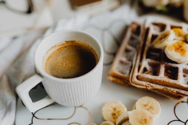 Piatto di waffle con fette di banana e una tazza di caffè