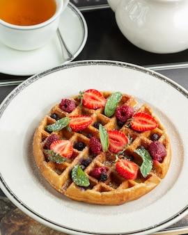 Piatto di waffle condita con fragole, lamponi, mirtilli e foglie di menta