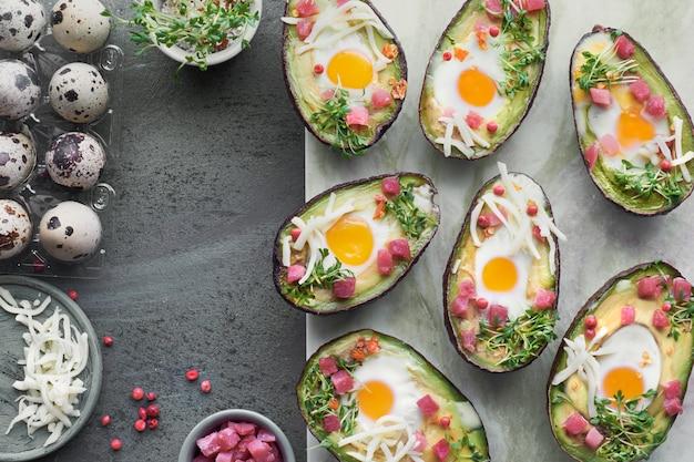 Piatto dietetico keto: avocado con cubetti di prosciutto, uova di quaglia, formaggio e germogli di crescione