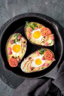Piatto dietetico keto: avocado con cubetti di prosciutto, uova di quaglia, formaggio e pomodorini su padella in ghisa di ferro